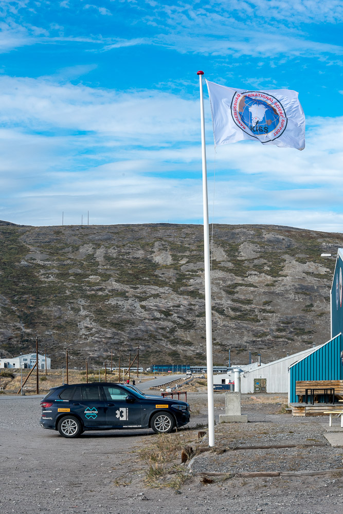 The KISS flag flies beside one of the Extreme E company cars.